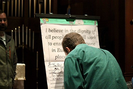 """An attendee signs onto the pledge stating """"I believe in the dignity of all people and I will work to ensure that everyone in Eureka has a safe place to call home."""" - FREDDY BREWSTER"""