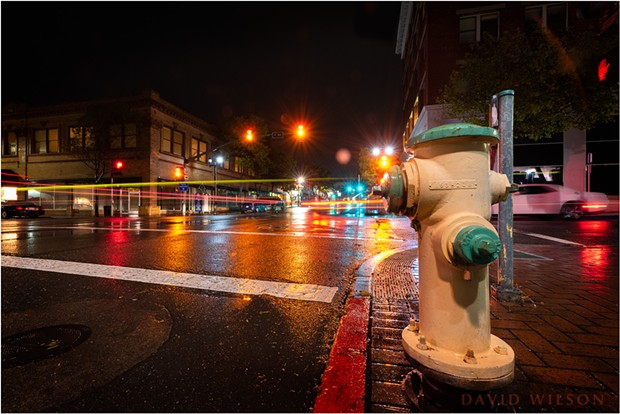 The fire hydrant sitting on the corner of 5th and F Streets in Eureka, California. The light streaks in the image are from cars going by. In long exposures such as this, the cars moved almost entirely through the frame while the shutter was open, causing their lights to become streaks. The driving cars themselves are not bright enough to see. - DAVID WILSON