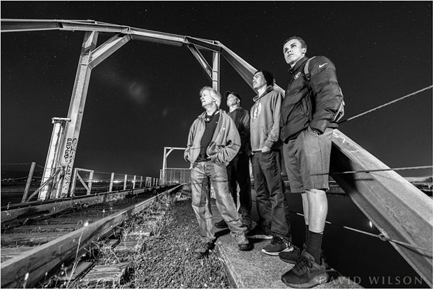 My son, my brother and his son and I wait beside the Eureka Slough railroad tracks. It doesn't always feel safe out there at night, whether due to thoughts of unfriendly people or ravenous beasts, so I was grateful to have the company of family while photographing. - DAVID WILSON