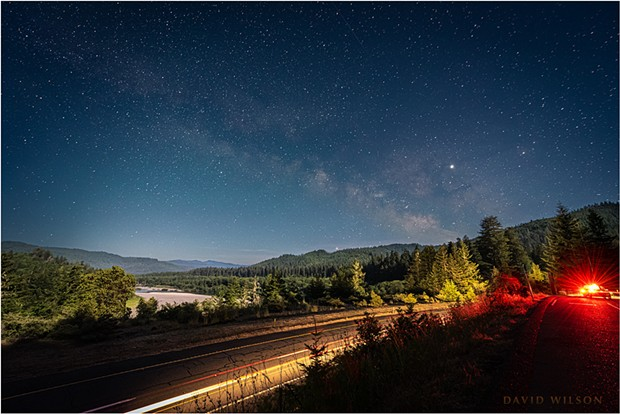 A nighttime view over US Highway 101 and the Eel River valley beneath the Milky Way as seen from a Vista Point in Humboldt County, California. A waxing half moon brightened the sky and cast its illumination on the landscape. The parked car of another night watcher added an unexpected red glow when it turned on its lights. - DAVID WILSON