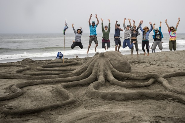 "The Northcoast Environmental Center team members took to the air when they finished their ""Lend a Hand, or Eight"" sand sculpture. It later won the People's Choice award. - PHOTO BY MARK LARSON"