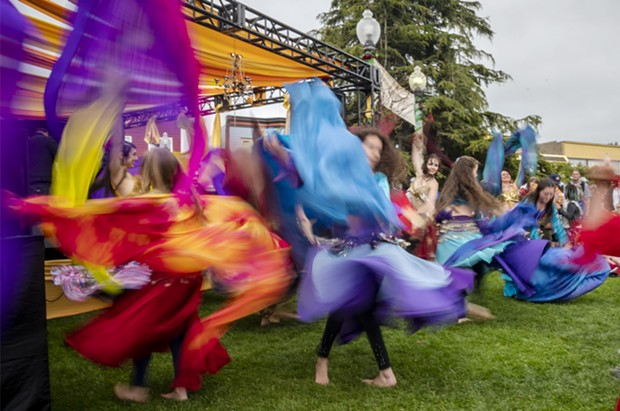 A slow shutter speed allowed the colorful costumes of the belly dancing group Ya Habibi in front the Enchantment Stage to blur in the photo. - PHOTO BY MARK LARSON