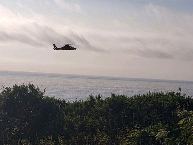 A MH-65 Dolphin helicopter conducts a cliffside rescue after a hiker became stranded near the base of the sea cliff in Patricks Point State Park in Trinidad, California, July 4, 2019. The hiker was hoisted aboard the Dolphin and transported to local emergency medical services with no reported injuries. - U.S. COAST GUARD PHOTO COURTESY OF ARCATA MAD RIVER AMBULANCE SERVICES
