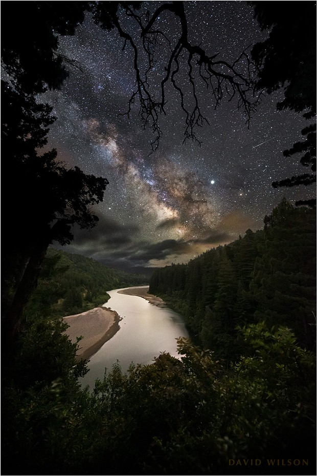 """""""A shooting star! Over near Jupiter!"""" I missed the meteor at the time, but not the magic of the night. Below us the Eel River glided between Redwood-covered hillsides under the night sky. I was with a former student and her friend and we played with our cameras while we stood in awe of the night. I found the meteor as I examined the photographs later. Humboldt County, California. - DAVID WILSON"""