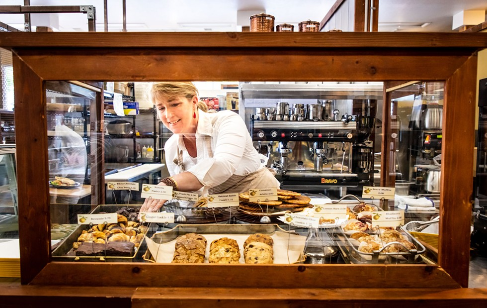 Owner Christine Silver fills the bakery case with treats. - AMY KUMLER