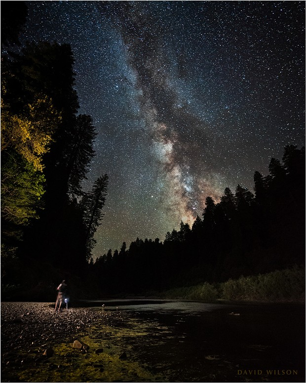 Small beneath the stars, a friend photographs the nightscape on the banks of the South Fork Eel River. Popular in the daytime, we had the site to ourselves. Part of the Milky Way's core is visible above the horizon, roughly that area with the greater detail and more reds and yellows. Humboldt County, California. - DAVID WILSON