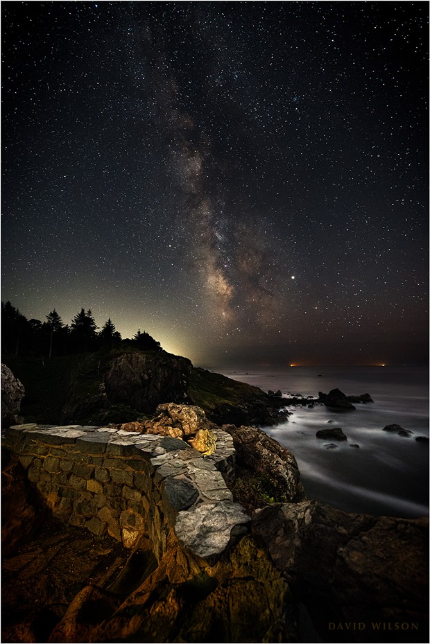 Ramparts stand watch over the great Pacific Ocean at the edge of the continent. The lights of a pair of fishing boats glow in the marine layer's gloom on the horizon. Patrick's Point State Park, Humboldt County, California. September 2019. - DAVID WILSON
