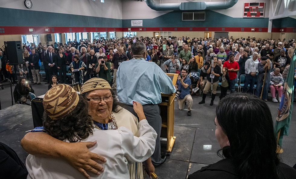 As Wiyot Tribal Chair Ted Hernandez closes the program, elder Cheryl Seidner hugs a member of the Wiyot Tribal Council. - BY MARK LARSON