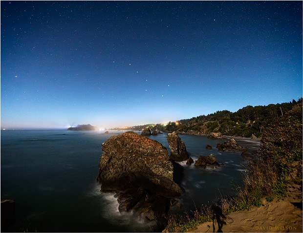 At the western edge of the North American continent, on the rough shores of the great Pacific Ocean, Trinidad, Humboldt County, California, sparkles in the moonlight under a starry sky. The Big Dipper and Polaris, the North Star, have been enhanced for recognizability. - DAVID WILSON