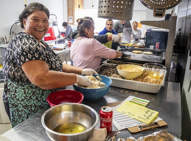 Dora Portillo (left) worked with the group of women volunteers in the kitchen assembly line. - MARK LARSON