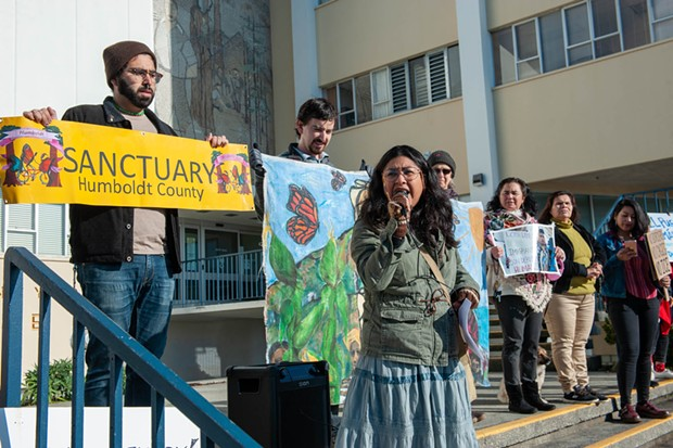 Brenda Perez emcees Centro del Pueblo's demonstration. - PHOTO BY MARK MCKENNA