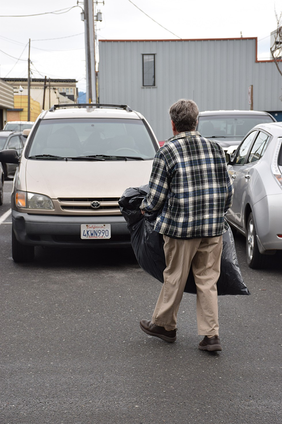 Robert Lohn with a garbage bag full of donated coats picked up from the North Coast Co-op in Eureka - PHOTO BY THADEUS GREENSON