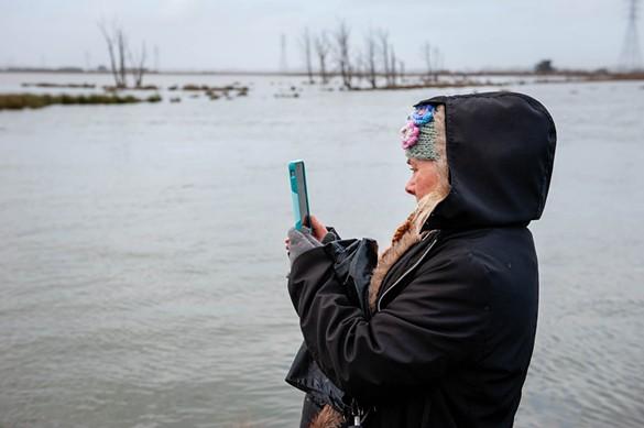 Sherry Van Fossen photographs the King Tide at the Arcata Marsh. - MARK MCKENNA