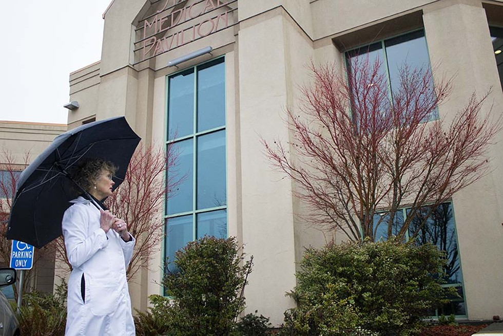 Kim Ervin walks by Shaw Medical Pavilion at Mad River Community Hospital on a rainy afternoon. - PHOTO BY THOMAS LAL