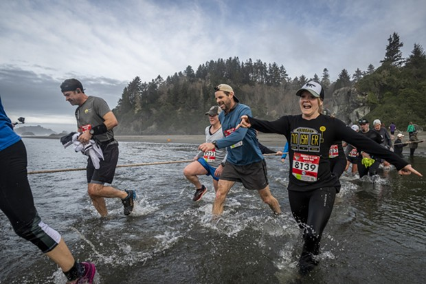 Andrea Carby, of McKinleyville, and a crowd of runners splashed their way across Little River. - MARK LARSON