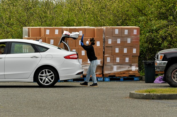 A Cooperation Humboldt volunteer loads a food box into the trunk of a car. - PHIL GUTIERREZ