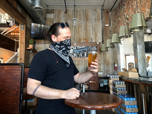 Dylan Powers, 40, assistant brewer, samples a new habanero Pilsner in the bar of Sage Plant Based Bistro. - NIGEL DUARA FOR CALMATTERS