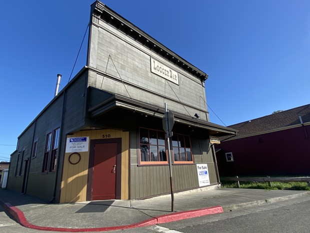 """The historic Logger Bar with """"for sale"""" signs. - ASHLEY HARRELL"""