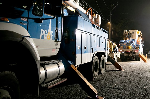 PG&E employees work to replace a nearly 100-year-old utility pole in Berkeley last year. - ANNE WERNIKOFF FOR CALMATTERS