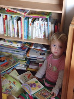 A child snuggles into her reading corner during child care. - PHOTO BY CAROL HARRISON