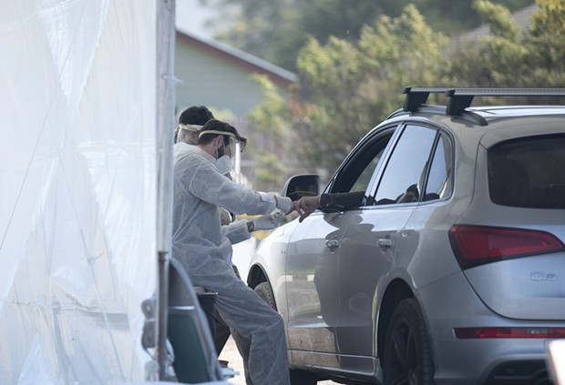 A phlebotomist takes a finger prick blood sample at a drive-through COVID-19 testing site in Bolinas on April 22, 2020. Bolinas is attempting to test the entire town in conjunction with a UCSF study, one of the first efforts of its kind in California. - ANNE WERNIKOFF FOR CALMATTERS