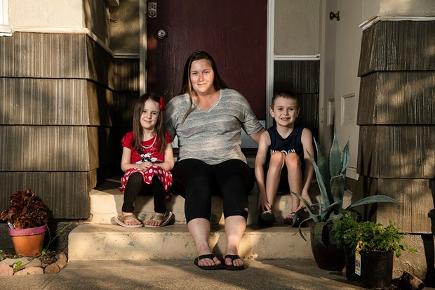 Kyla Hill, 5, left, Rebecca Hill, center, and Kaden Hill, 7, right, sit for a portrait at their home in Chico on July 23, 2020. Rebecca has to balance what's best for her children's education with their safety and that of her immuno-compromised husband. - SALGU WISSMATH/CALMATTERS