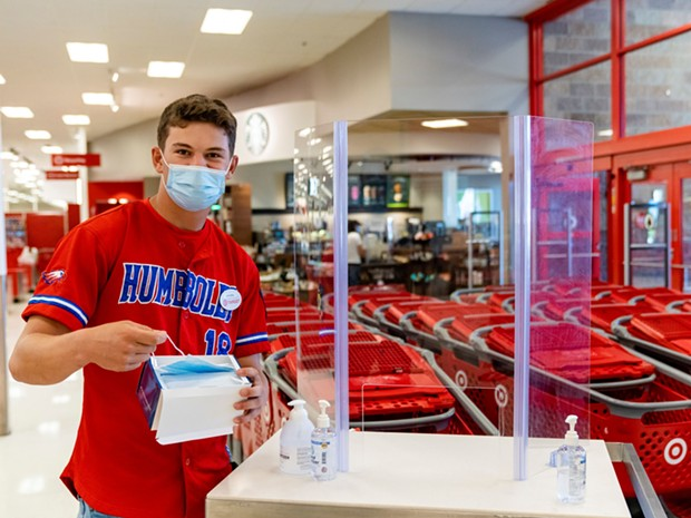 Target employee and Eureka High School senior Hayden Bode provides masks and hand sanitizer for shoppers who do not have one at no cost. - ZACH LATHOURIS