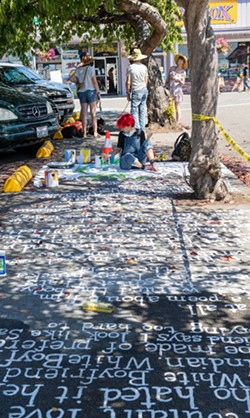 This year's festival included poetry painted on the sidewalks, such as this piece written and painted by Harvey Mitchell. - PHOTO BY MARK MCKENNA