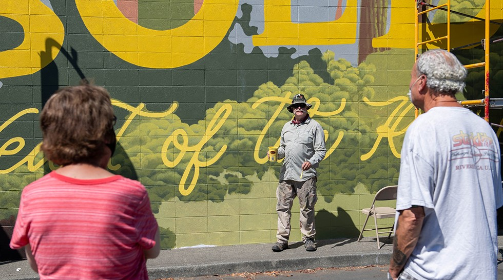 "Local copper artist Scott Hemphill talks with a couple taking in the murals during the festival. Hemphill was helping with the lettering on Ellie Gainey's mural ""Heart of the Redwoods,"" located on the side of the Toy Box. It was the largest mural of this year's festival. - PHOTO BY MARK MCKENNA"