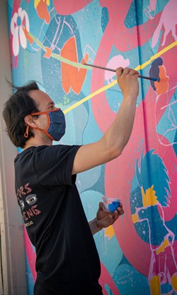 Jose Moreno finishes one of his two murals painted on garage doors in the alley off Henderson Street between E and F streets. - PHOTO BY MARK MCKENNA