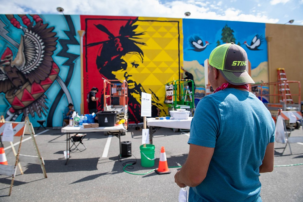 """Alme Allen looks at his nearly completed mural """"Arareethívthaaneen"""" on the back wall of the Discovery Shop on the last day of the festival. - PHOTO BY MARK MCKENNA"""