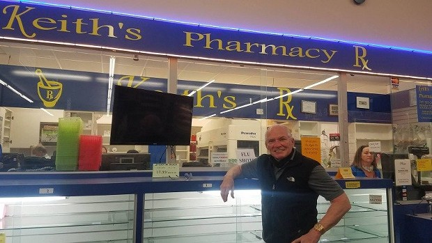 Keith Lorang poses in front of empty shelves at his pharmacy which is closing at the end of Friday. - LAUREN SCHMITT, COURTESY OF KMUD