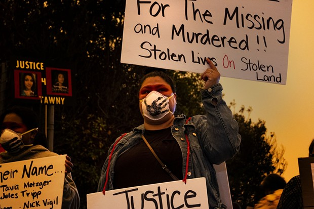 Veronica Jones holds signs asking for justice for those who are missing or murdered. - KRIS NAGEL
