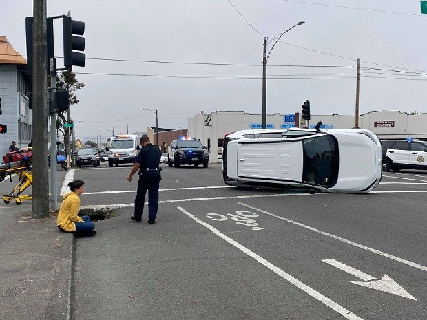 The driver of the white vehicle sits on the curb while an officer stands nearby. - MARK MCKENNA