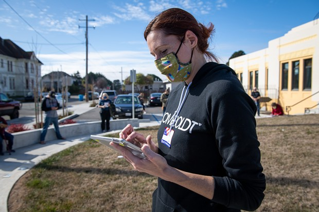 Voter Assistance Center Manager Talvi Fried checks to see if people waiting in line are at their assigned precinct in Eureka. - MARK MCKENNA