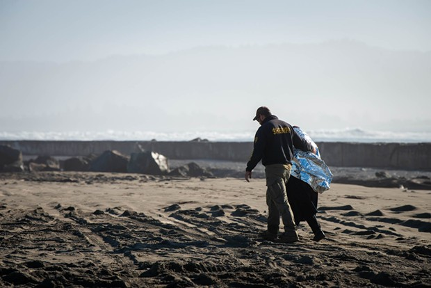A member of the Humboldt County Sheriff's Office walks with a family member of the woman as she was pulled from the surf and was administered CPR.