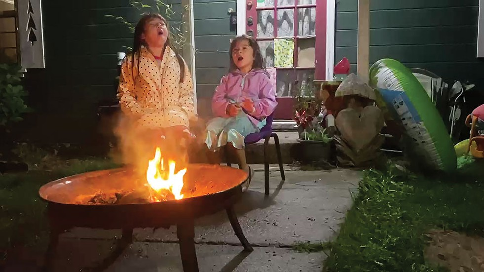 Right: Alexis Wickizer (left) and her sister Shelby howl by the fire in support of healthcare workers and first responders - PHOTO BY ASHLEY HARRELL