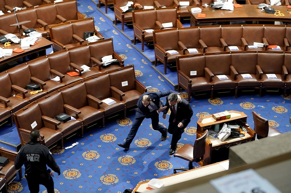 Members of Congress run for cover as insurrectionists try to enter the House chamber during a joint session of Congress on Jan. 6. - ALEX GAKOS / SHUTTERSTOCK