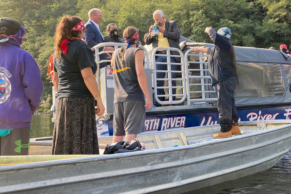 Berkshire Hathaway Energy CEO William Fehrman smells a bottle of toxic algae pulled from above one of the four hydroelectric dams on the Klamath River while speaking to protesters at a blockade on Aug. 28, 2020. - SAMMY GENSAW