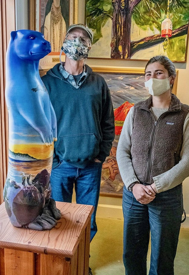 Jeff Black and Michelle Kunst standing by Maureen McGarrys North Coast Otter sculture at the Simmons Gallery. - TRINIDAD COASTAL LAND TRUST