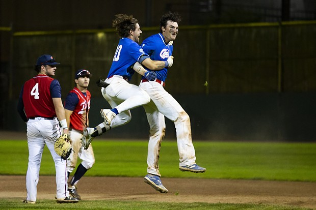 Crabs third baseman David Morgan (No. 20) leaps into the air and hugs teammate Andrew Allanson (No. 22) as he jumps up after hitting the walk-off base hit to win the game against the Redding Tigers in the bottom of the 11th inning on July 20, 2021. - THOMAS LAL