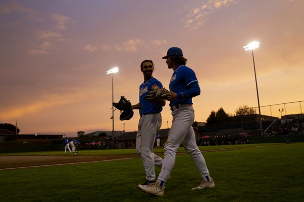 Outfielders Tyler Ganus (Left) and Josh Lauck (Right) head out to take the field as the sun begins to set over Arcata Ballpark on July 27, 2021. - THOMAS LAL