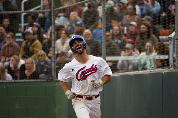 Crabs outfielder Tyler Ganus smiles as he jogs back to the dugout after scoring against the Alaska Goldpanners on August 4, 2021 at Arcata Ballpark. - THOMAS LAL
