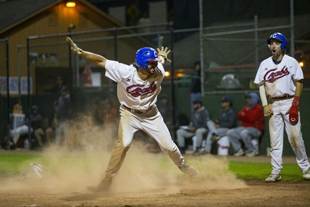 """Outfielder Tyler Ganus throws his arms up in a """"safe"""" motion after sliding across home plate to score against the Alaska Goldpanners on August 4, 2021. - THOMAS LAL"""