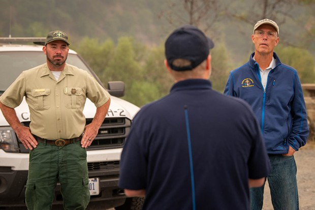 North Coast Congressman Jared Huffman (right) listens to a briefing at an air base set up near Willow Creek, west of the Monument Fire. - MARK MCKENNA