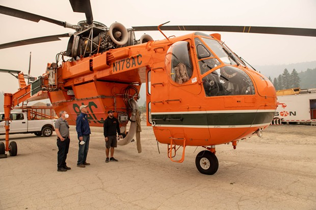 North Coast Congressmember Jared Huffman looks at an Erickson Air-Crane, which can pull 2,600 gallons of water from a river or pond in 45 seconds, while touring a fire base in Willow Creek. - MARK MCKENNA