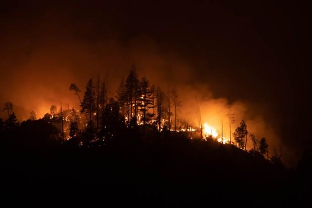 The Monument Fire burns a hilltop south of the Trinity River near Big Bar. - MARK MCKENNA