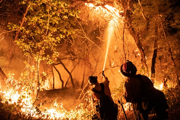 Firefighters from multiple agencies, including some that were pulled off the Monument Fire defended houses at the end of Enchanted Creek Lane on Monday. - MARK MCKENNA