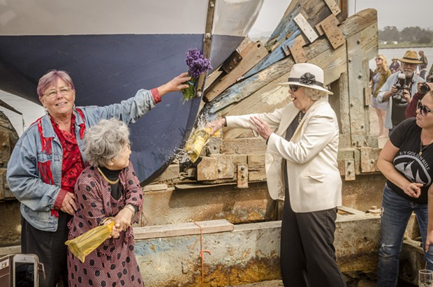 Sally Willowbee (left), Hiroshima atomic bomb survivor Shigeko Sasamori and Kitty Bigelow Benton, daughter of the original captain of the Golden Rule, apply the traditional christening prior to its launching on Saturday, June 20 at the Zerlang & Zerlang  boat yard on the Samoa peninsula. Willowbee is a daughter of one of the original Golden Rule crew members. - MARK LARSON