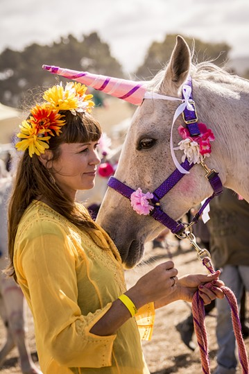 """Julie Vinum, of Blue Lake, waited with her """"unicorn,"""" Gracie, to begin the Blue Lake Saddle Club's rides for children. It was the first year for the club's petting zoo and horseback ride fundraiser at the Medieval Festival of Courage in Blue Lake on Saturday, Oct. 3. - MARK LARSON"""